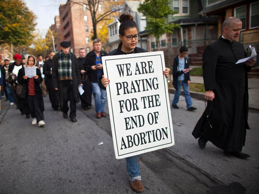 Image: A woman holds a sign during an anti-abortion protest march to the Choices Women's Medical Center in Queens