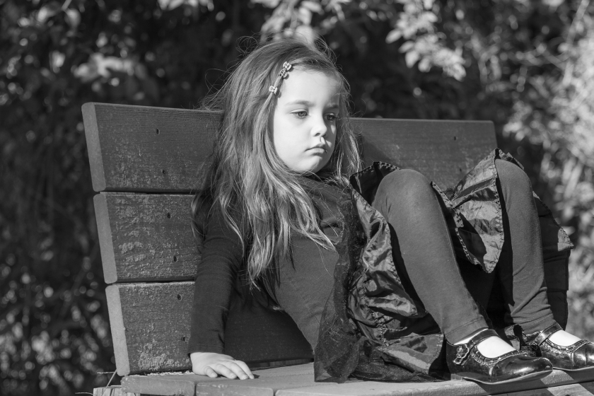 tired or bored little girl sitting on a bench, black and white i